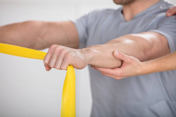 Close-up Of A Physiotherapist Giving Man A Training With Exercise Band